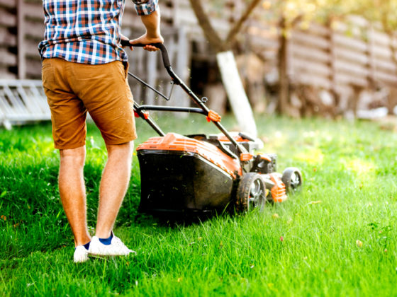 Portrait of man cutting grass in his garden using a gasoline powered lawn mower